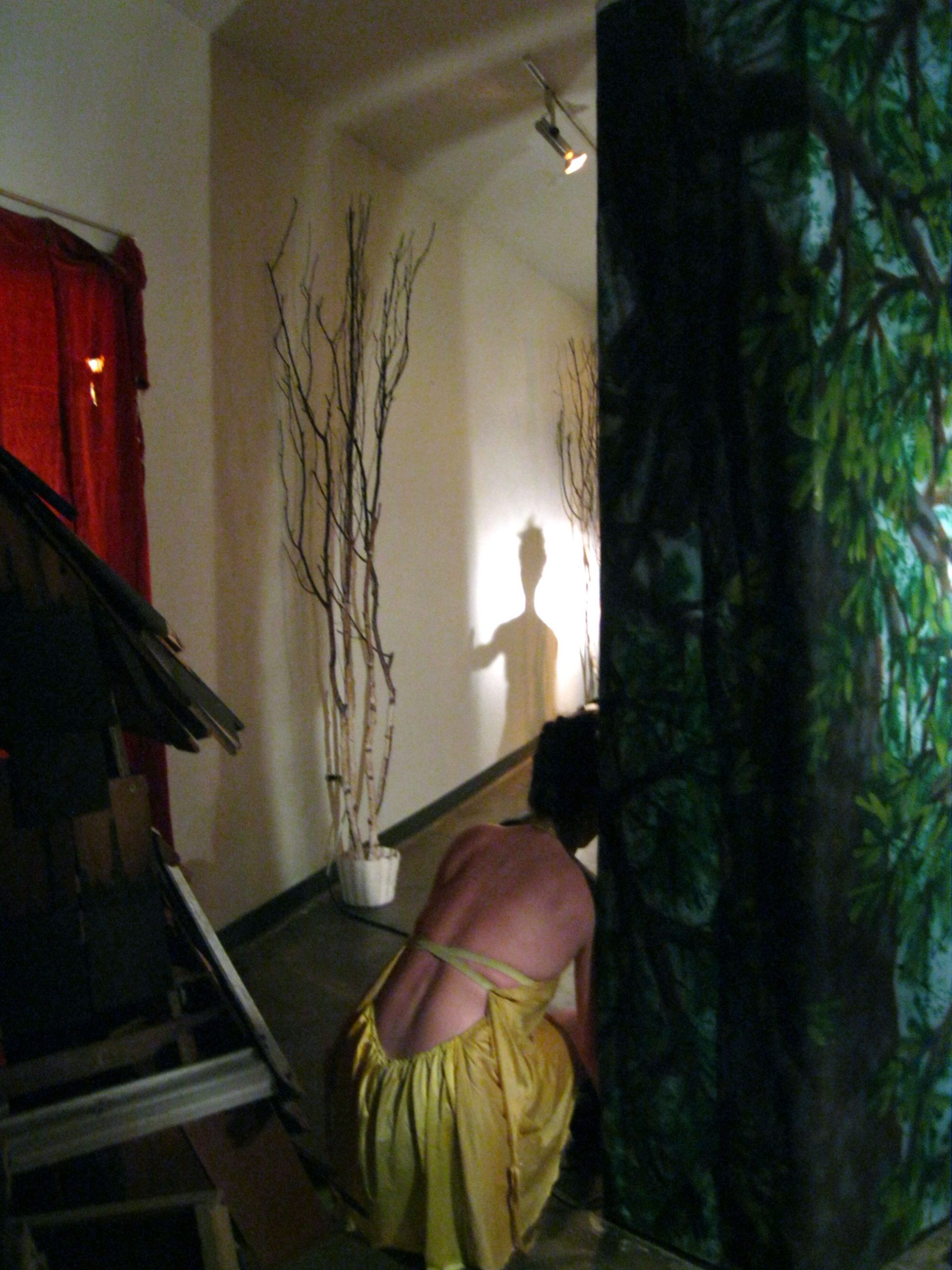 dancer crouching on the floor next to part of installation